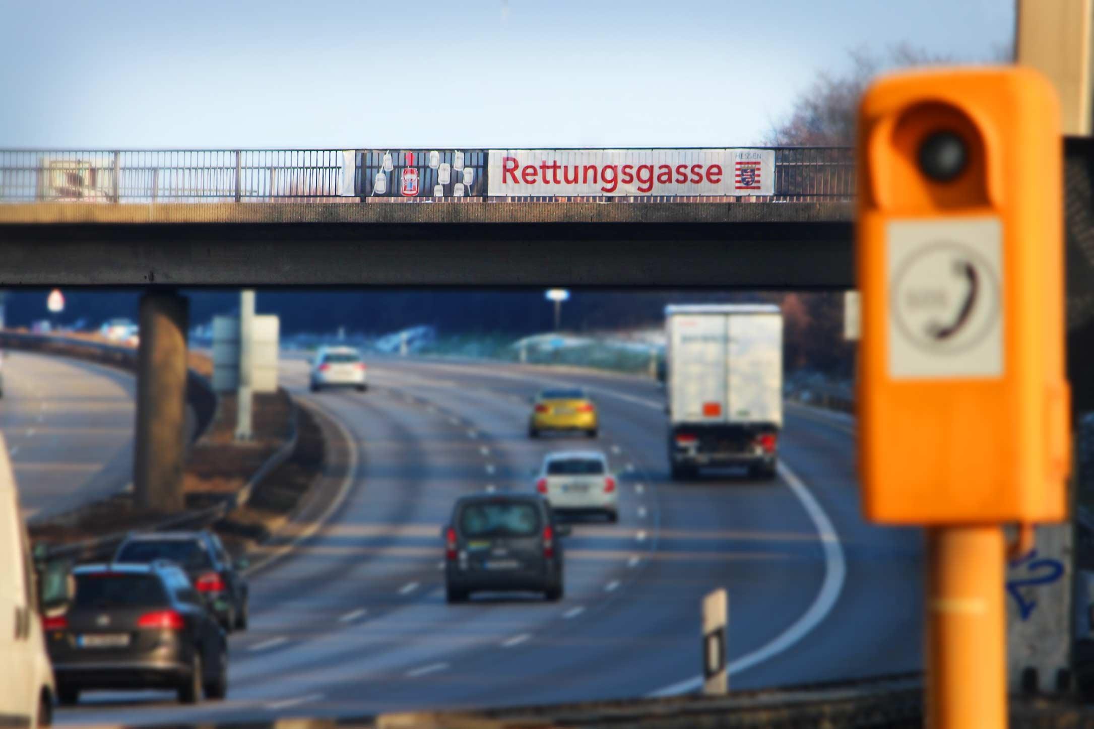 Rettungsgasse-Banner an einer Brücke über der Autobahn