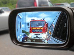 Blick in den Außenspiegel, ein Einsatzfahrzeug nähert sich