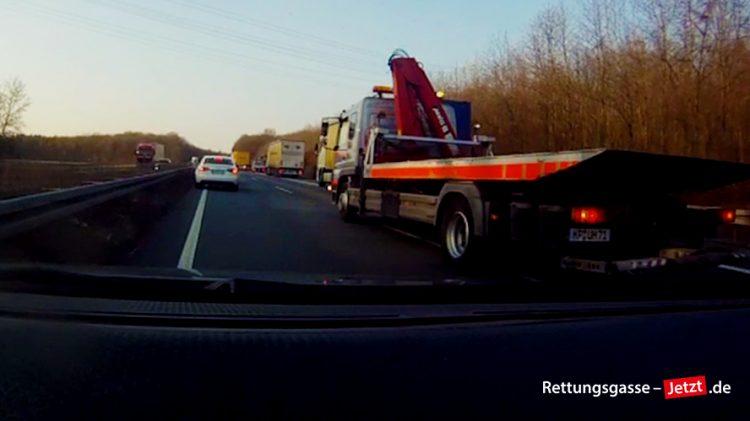 Im Stau auf der Autobahn bilden die Fahrzeuge für einen Abschleppwagen die Rettungsgasse