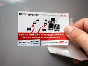 Rettungsgasse-Aufkleber in Form einer Visitenkarte wird auf einen Lack-Untergrund geklebt
